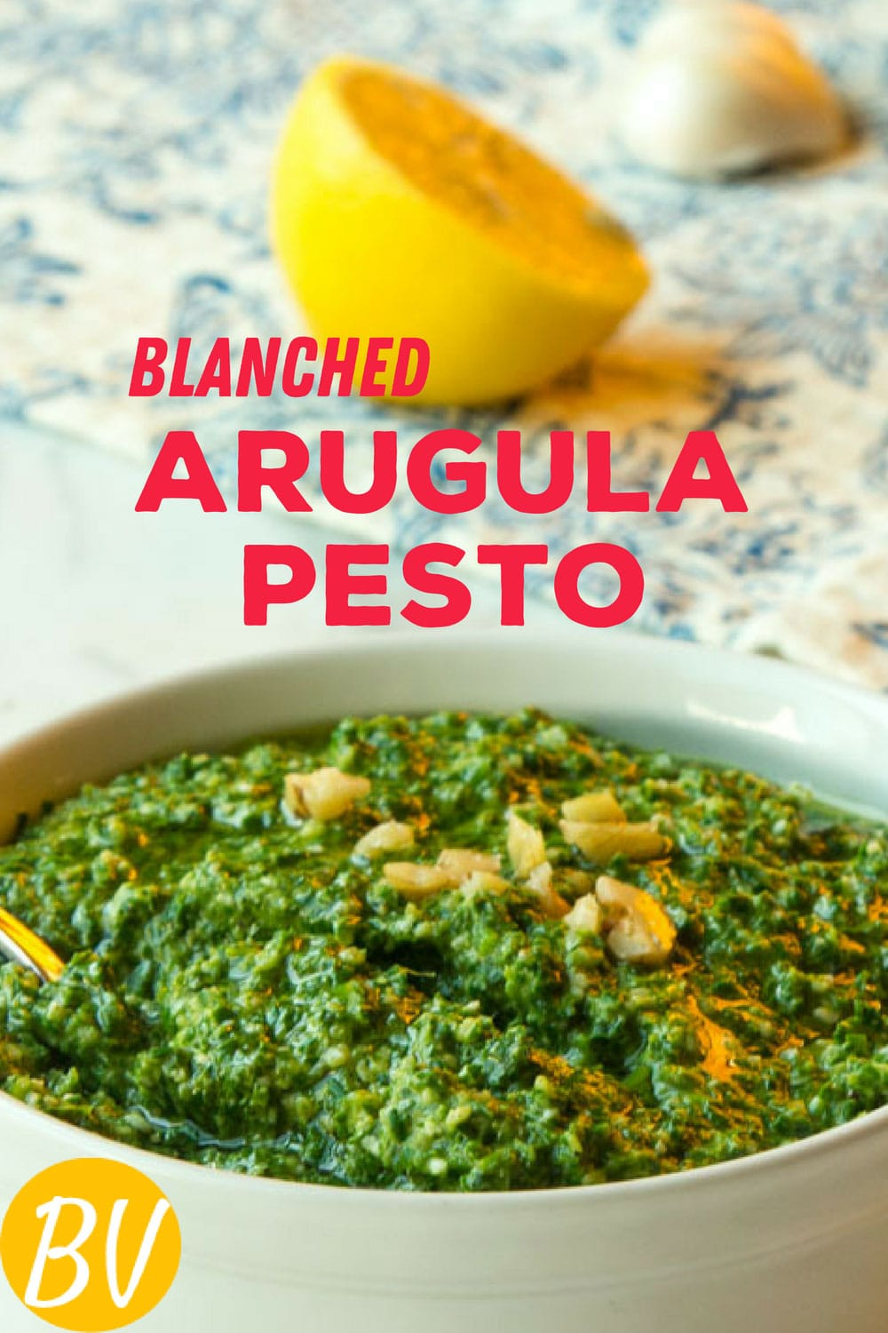 Arugula Pesto made with blanched arugula results in mellower flavor, succulent texture, and bright green color with minimal use of oil. It\'s wonderful with pasta, toast and eggs, sandwiches, boiled potatoes, or as a base for a pesto pizza. #pesto #arugula #spread #condiment #pasta #vegetarian #parmesan #greens #toast
