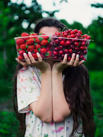 a woman balances berries in her hands